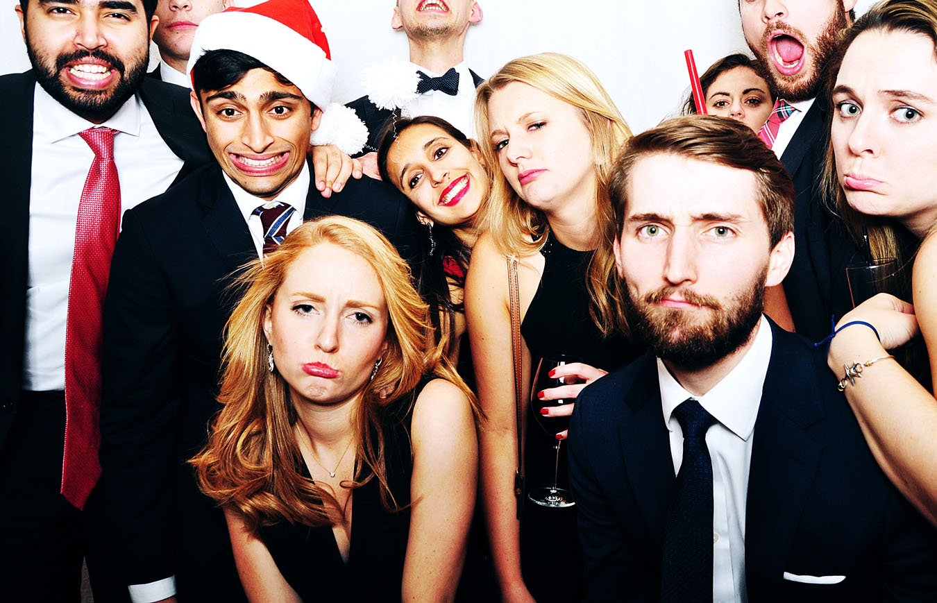 Corporate holiday party photobooth image in Massachusetts - people wearing santa hats and having drinks