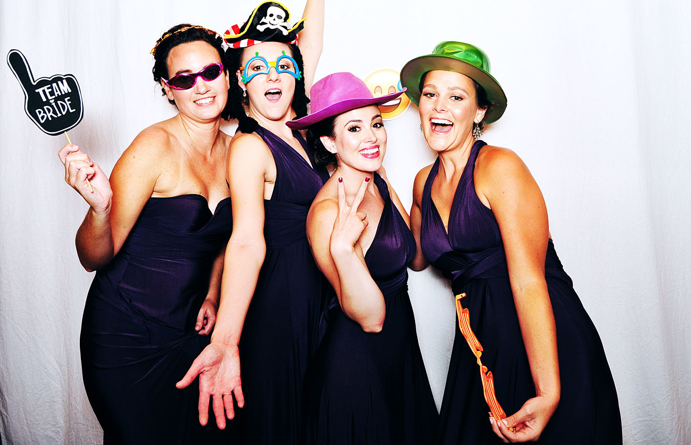 CT Photobooth image of four girls - wearing masks and using props - girls are bridesmaids at a wedding